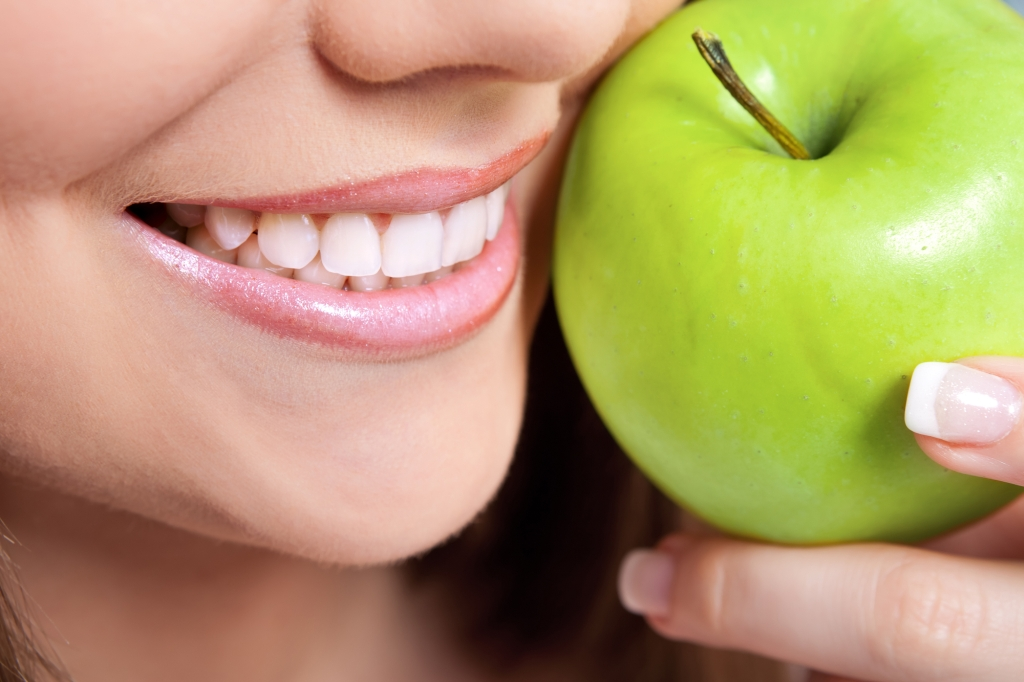 healthy teeth and green apple, close up